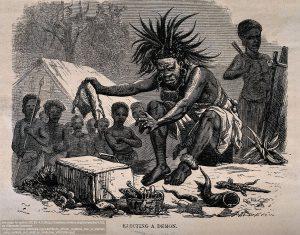 アフリカのメディスンマン(呪医)/ シンボルや小動物を用いて病(悪魔)を追い払っている。